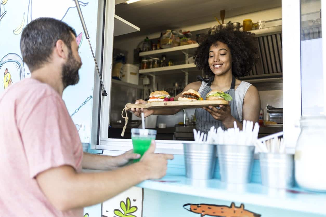 Woman serving man food from food truck